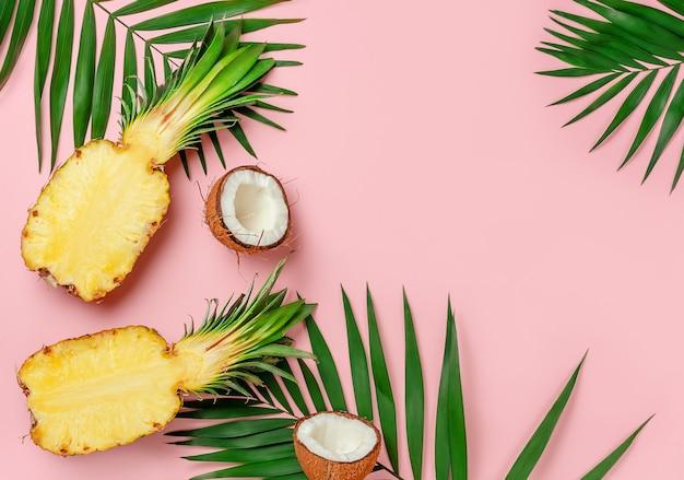 분홍색 여름 배경에 파인애플과 코코넛이 반으로 줄었습니다. 상위 뷰, 복사 공간입니다.