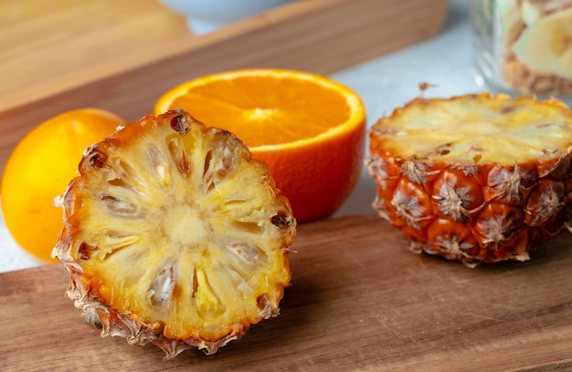 Halved pineapple and orange on wooden board