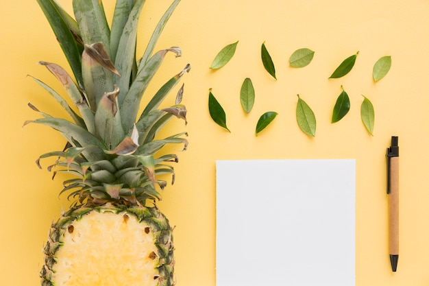 Halved pineapple with leaves; pen and white paper on yellow background