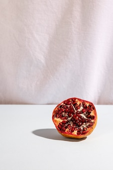 Halved pomegranate on desk in front of white curtain