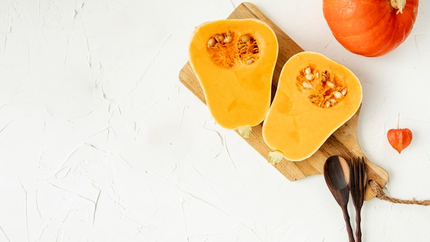 Halved pumpkin on cutting board with copy space