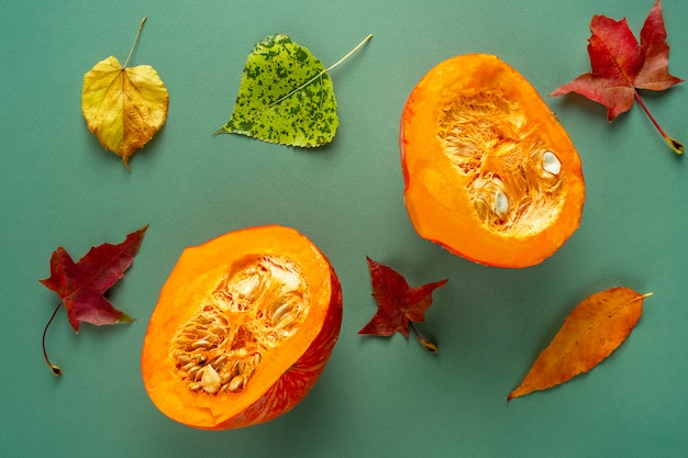 Halved pumpkin with autumn leaves on green background