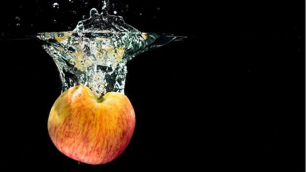 Halved red apple falling into water splash on black background