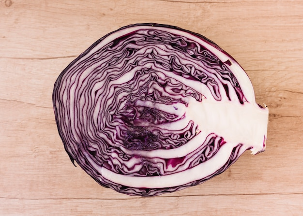 Halved red cabbage on wooden background