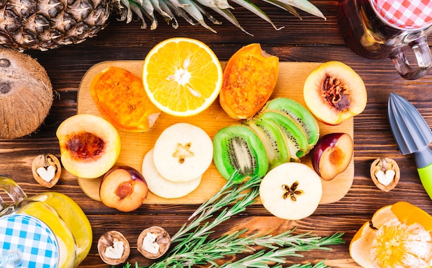 Halved; slices of fresh fruits; walnuts and rosemary on wooden table