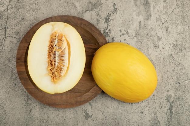 Melone giallo delizioso diviso in due e intero sul piatto di legno.
