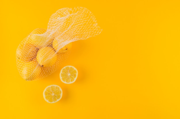 Halved and whole ripe juicy lemons on yellow background