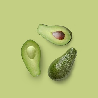 녹색 배경에 반쪽과 전체 녹색 신선한 아보카도가 격리되어 있습니다.
