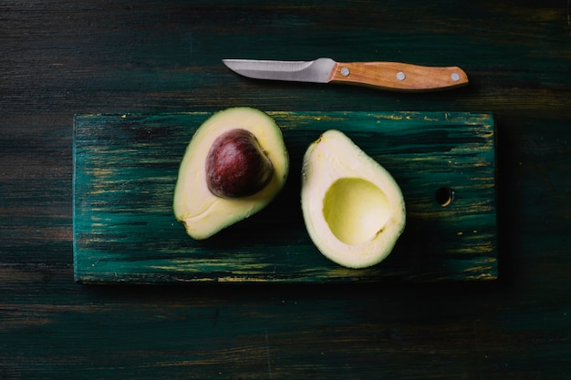 Halves of avocado on a cutting board flat lay