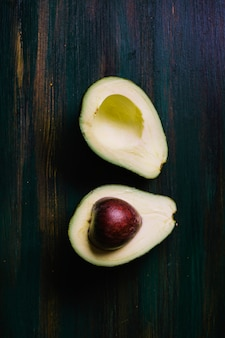Halves of avocado on a cutting board top view