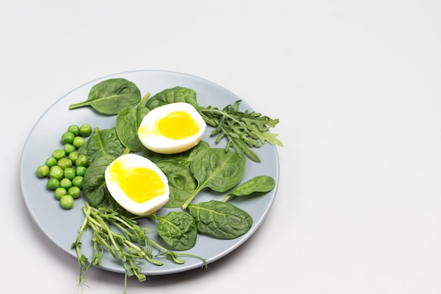 Halves of boiled chicken egg spinach leaves arugula and green peas
