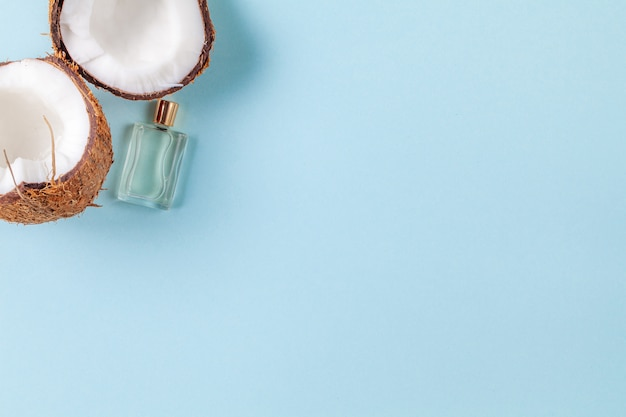 Halves of chopped coconut on blue background with small bottle of oil