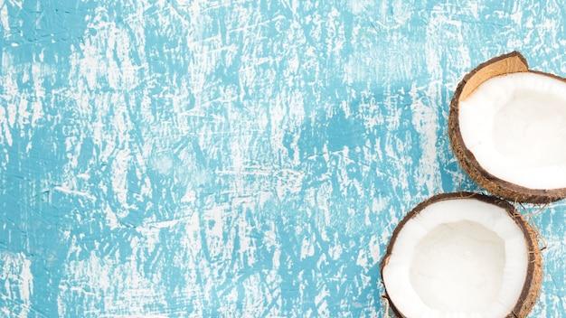 Halves of coconut fruit on blue background