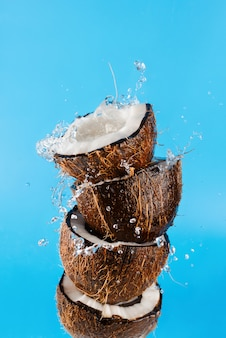Halves of coconuts with splashing water on blue background, selective focus