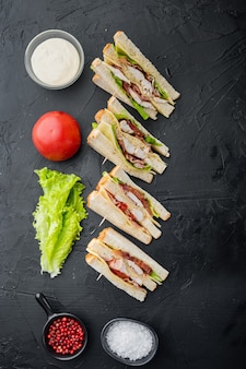 Halves of fresh club sandwiches, on black background, top view
