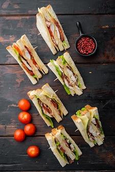 Halves of fresh club sandwiches, on dark wooden background, top view