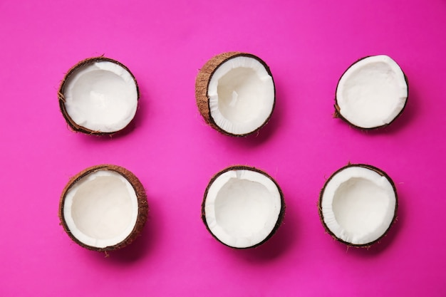 Halves of fresh coconuts on color background
