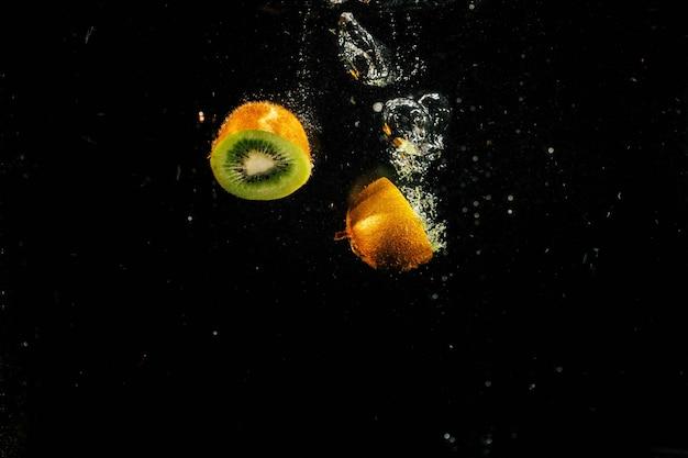 Halves of green kiwi fall in aquarium
