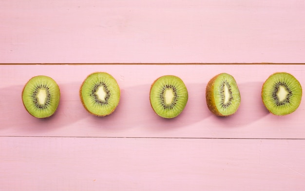 Halves of kiwi fruit on pink background