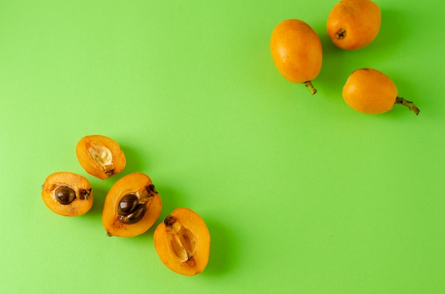 Halves of a loquat fruits on a bright green