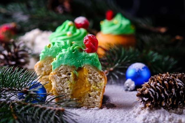 雪に覆われたお祭りの森で、タンジェリンクルドを詰めたクリスマスマフィンの半分。新年とクリスマスのお祝いのデザート。