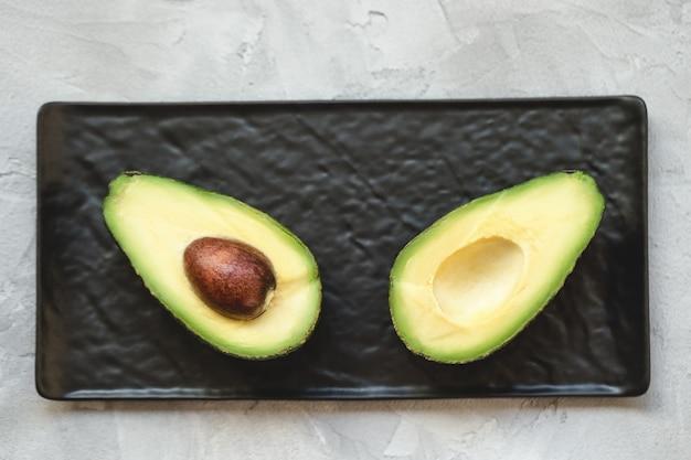 Половинки свежего авокадо на черной сервировочной тарелке