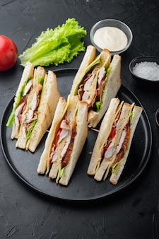 黒いテーブルの上に、新鮮なクラブサンドイッチの半分