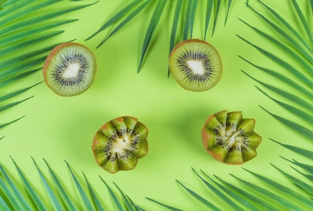 열대 나뭇잎과 녹색 배경에 신선한 녹색 키위 반쪽, 컬러 과일 배치 프리미엄 사진