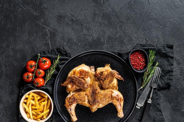 Половинки жареной сочной курицы с золотисто-коричневой корочкой на сковороде. черный фон. вид сверху. пространство для текста