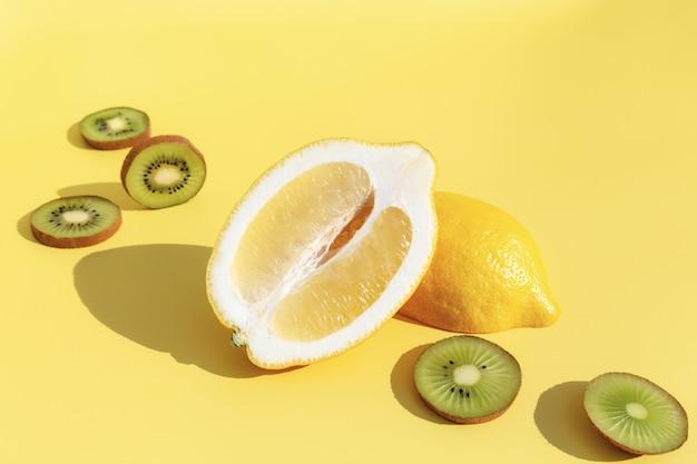 影付きのレモンの半分、黄色の背景にスライスしたキウイカット。健康的な食事、旅行または休暇の概念