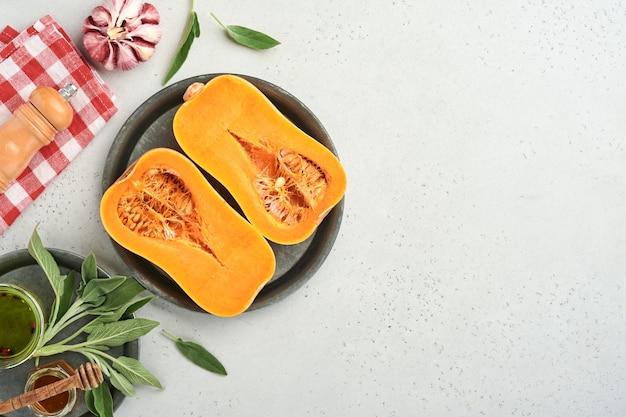 白いスレート、石またはコンクリートの背景にセージの葉、色とりどりのペッパーガーリック、蜂蜜、塩、コショウを添えた生の有機バターナッツスカッシュの半分。食品の背景。コピースペースのある上面図。