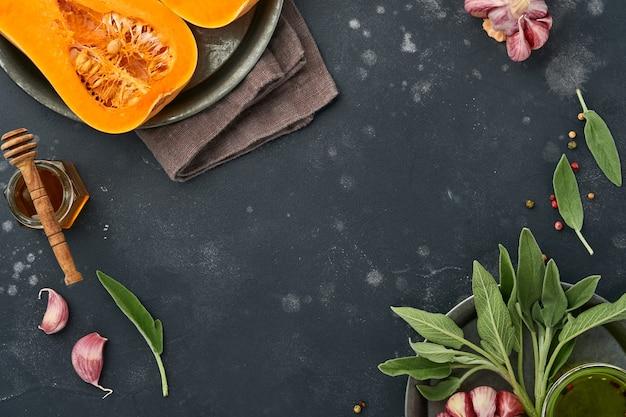 黒のスレート、石またはコンクリートの背景にセージの葉、色とりどりのペッパーガーリック、蜂蜜、塩、コショウを添えた生の有機バターナッツスカッシュの半分。食品の背景。コピースペースのある上面図。