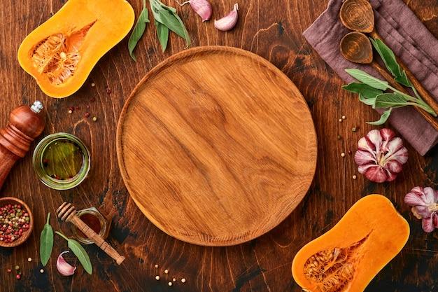 古い木製の背景にセージの葉、色とりどりのペッパーニンニク、蜂蜜、塩、コショウと生の有機バターナッツスカッシュの半分。食品の背景。コピースペースのある上面図。