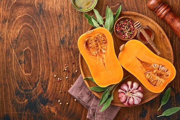 古い木製の背景にセージの葉、色とりどりのペッパーガーリック、蜂蜜、塩、コショウを添えた生の有機バターナッツスカッシュの半分。食品の背景。コピースペースのある上面図。