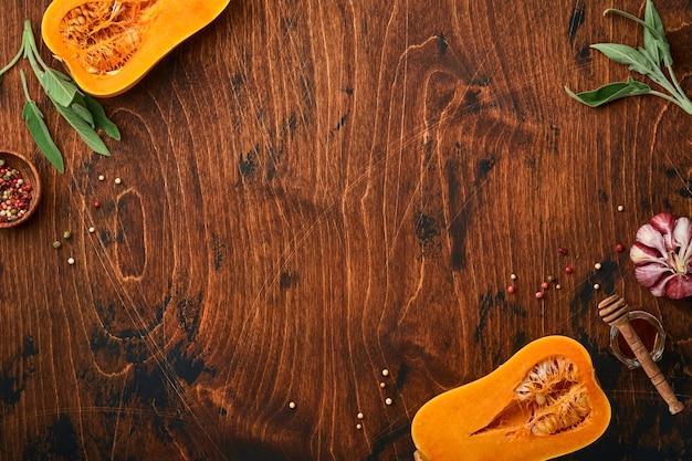 古い木製の背景にセージの葉、色とりどりのペッパーニンニク、蜂蜜、塩、コショウを添えた生の有機バターナッツスカッシュの半分。食品の背景。コピースペースのある上面図。