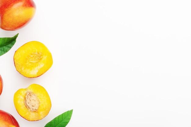붉은 육즙이 많은 복숭아 천도복숭아와 흰색 배경에 잎이 있는 신선한 과일의 절반. 유기농 건강 여름 음식. 평평한 위치, 복사 공간.