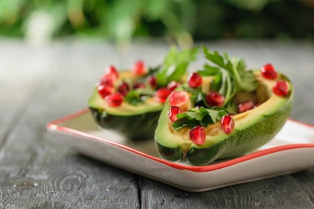 Половинки спелых авокадо с зернами граната и травы в миску на деревянном столе. вегетарианская кухня для похудения.