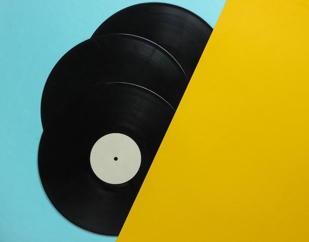 Половинки виниловых пластинок на синем желтом фоне. ретро музыкальные альбомы