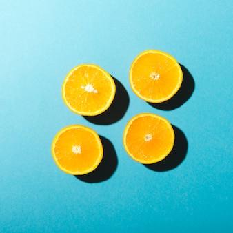 Halves of oranges on blue background