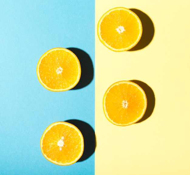 Halves of oranges on blue and yellow background