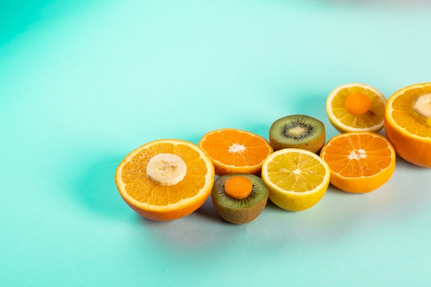 Halves of oranges kiwi and lemons on a blue table
