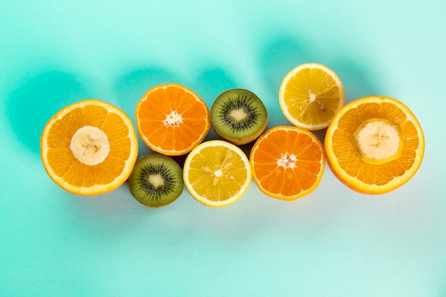 Halves of oranges kiwi and lemons on a blue table