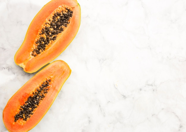 Halves of papaya fruit with copy space