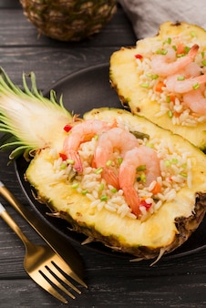 Halves of pineapple with shrimps and golden cutlery