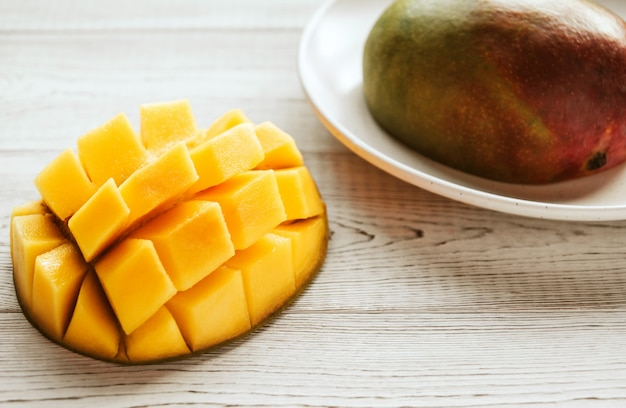 Halves of ripe mango on a white plate on a white wooden textured table copy space.