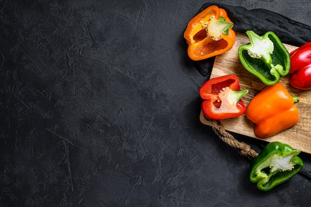 Halves of sliced orange, green and red sweet peppers. black background. top view. space for text