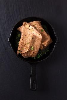 ハムとチーズクレープアイアンフライパンで黒いスレート背景