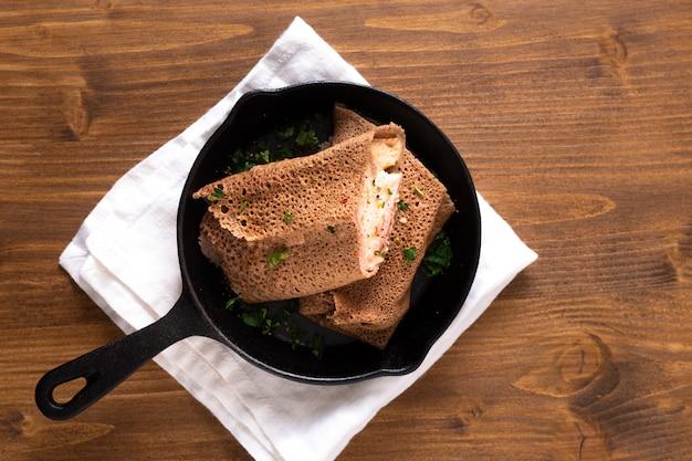 ハムとチーズクレープの鉄のフライパンでウッドの背景にキャスト
