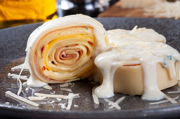 白いパルメザンソースをトッピングしたハムとチーズのロンデッリ