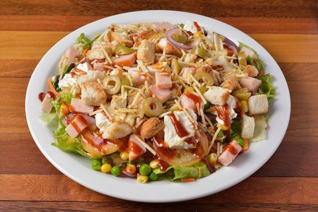 Салат с ветчиной и сыром на белой тарелке над деревянным столом.